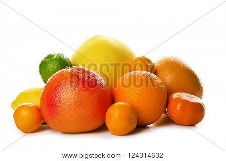 A heap of mixed citrus fruit including a grapefruit, oranges, lemons, clementines, tangerines, limes and a pomelo fruit isolated on a white background, close up