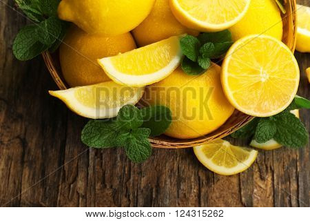 Fresh lemons with green leaves in bowl on wooden table, top view