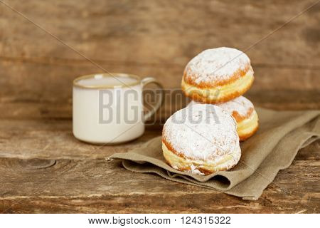 Delicious sugary donuts with cup of coffee on wooden background