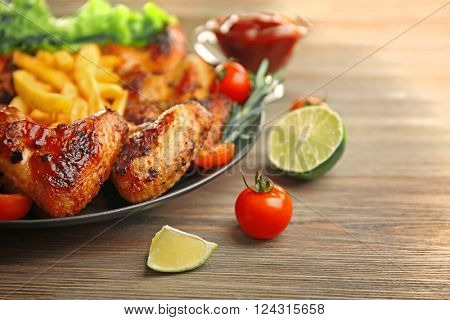 Grilled chicken wings with French fries, garden-staff and tomatoes on plate