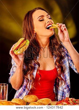 Girl eats with relish fastfood big hamburger and fried potatoes .