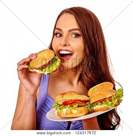 Girl holding and eating several hamburgers. Fastfood concept .