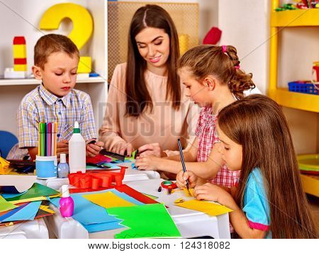 Children with teacher woman painting on paper at table  in  kindergarten . Kids team.