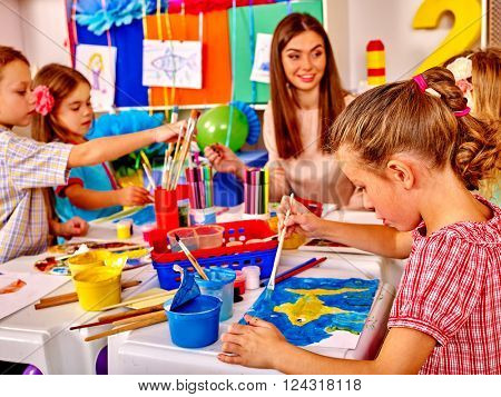Children with teacher woman painting on paper and communicate with each other at table  in  kindergarten .