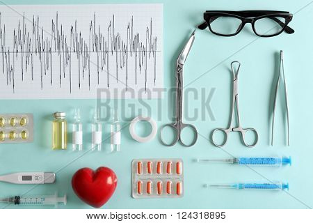 Doctor table with medical items and pills, top view