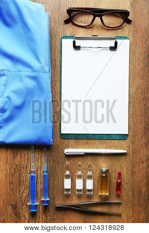 Doctor table with medicines and uniform, top view