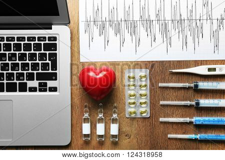 Doctor table with laptop, medicines, cardiogram and red heart, top view