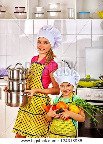 Child in cooking hat holding vegetable at kitchen. Children learn to cook