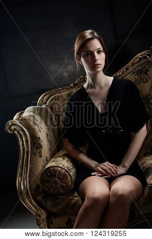 Elegant young woman sitting on baroque sofa, looking at camera.