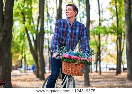 Happy handsome young man looking up ride on bike in park outdoor.