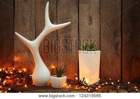 Decorative figurine with green plants in white pots on wooden background