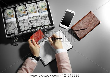 Businessman writing in notebook with case full of money