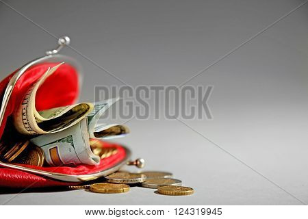 Open red purse with dollar banknotes and coins on grey background