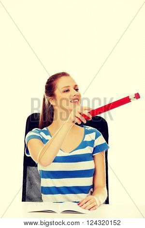 Teenage woman pointing for something with a huge pen