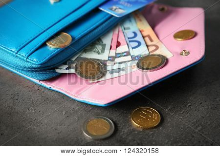 Blue wallet with euro bills on the grey background
