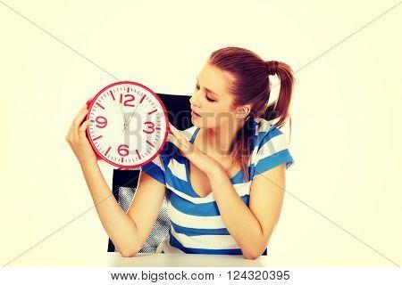 Teenage woman looking at clock