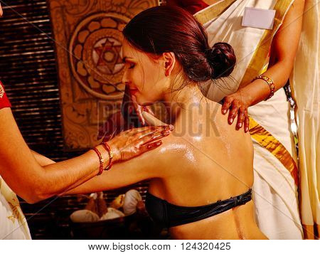 Woman having Ayurvedic spa shoulders massage. Pouring milk.
