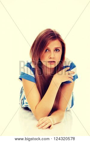 Teenage sad woman lies on the floor