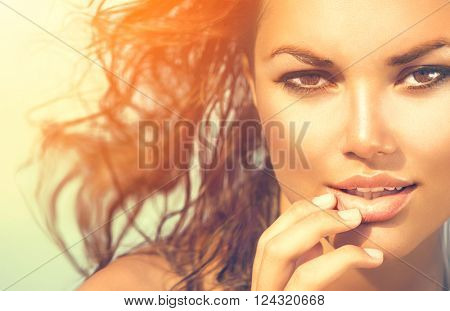 Beauty Sunshine Girl Portrait. Beautiful Model Woman over sea. Sunny Summer Day under the Hot Sun on the Beach. Ocean. Vacation concept.
