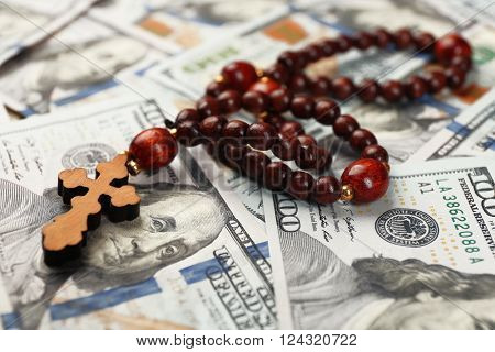 Rosary beads on money background, closeup
