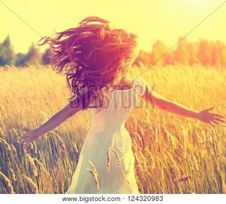 Beauty Girl Outdoors enjoying nature, raising hands. Beautiful Teenage Model girl with long healthy
