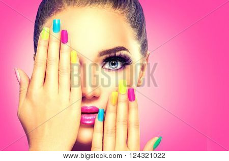 Beauty Girl Face with Colorful Nail polish. Colourful Studio Shot of young Woman. Vivid Colors. Colourful Manicure and fashion Makeup. Rainbow Colors. Beautiful lady touching her face