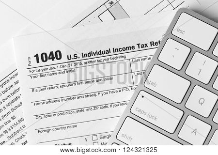 1040 Individual Income Tax Return Form for 2015 year with a computer keyboard on the white desk, close up
