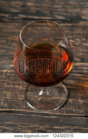 vintage cognac in large round glass on the old wooden background closeup top view