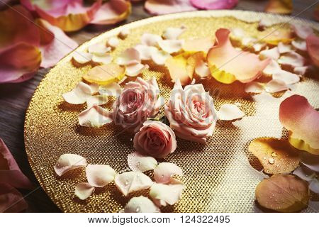 Pink and yellow rose petals in golden bowl with water on wooden background