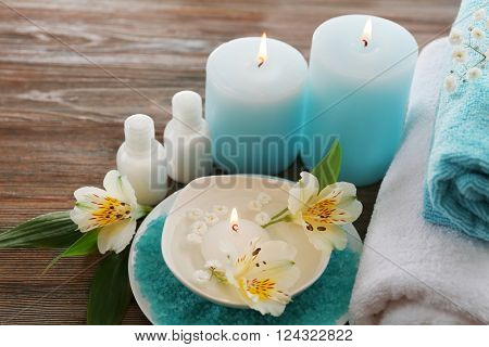 Spa still life with flowers and candlelight on wooden table closeup