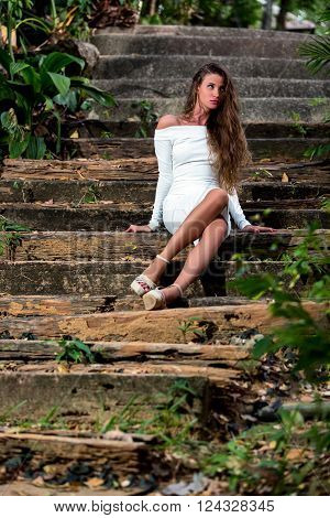 Beautiful Girl Sitting On Stairs In The Tropical Park