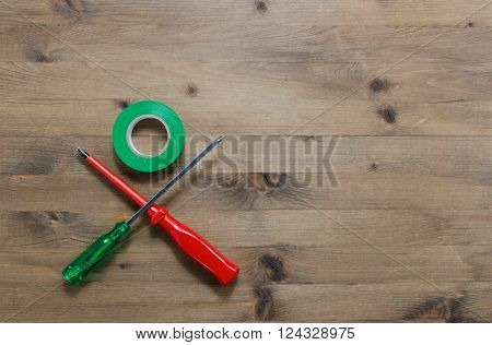 colored screwdrivers with duct tape on wooden table