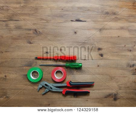 colored screwdrivers duct tape and pliers on wooden table
