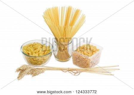 Uncooked dried long pasta in glass jar macaroni in glass bowl pasta seashell shaped in plastic tray and bundle of wheat spikes on a light background