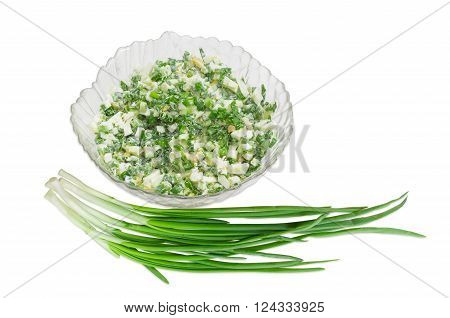 Spring salad with chopped green onions, boiled eggs and sour cream in a glass salad bowl and a bunch of green onions on a light background