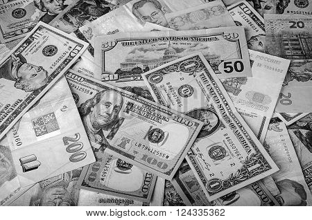 Balck and white photo of a collection of foreign currencies from countries spanning the globe. Many currencies as background concept global money. Soft selective focus and shallow depth of field