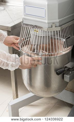chef is preparing cake mix in industrial bread mixer- kneading machine