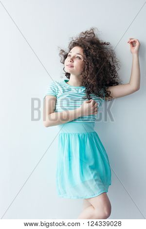 A young girl of Caucasian appearance dancing and dreams of a bright room on a summer day. Wavy curly hair and a blue dress. Rest and be happy.