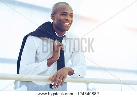 Successful businessman. Low Angle view of cheerful young African man in shirt and tie looking away and smiling