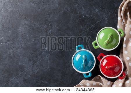 Colorful saucepans on stone table background. Top view with copy space