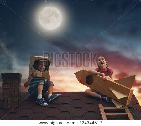 Children on the background of moon sky. Child boy in an astronaut costume and child girl with toy rocket standing on the roof of the house and looking at the sky and dreaming of becoming a spacemen.