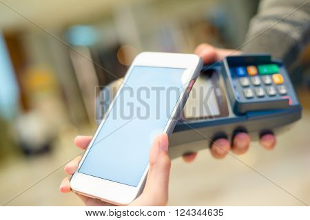 Woman using mobile phone to pay