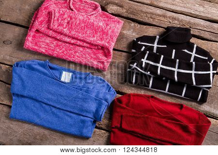 Lady's bright and dark sweaters. New sweaters on old floor. Bright clothing on old table. Sweaters selection at retro boutique.