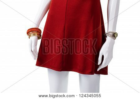 Wrist accessories on mannequin's hand. Female mannequin with new bracelets. Bijouterie that matches red dress. Fashionable accessories on sale.