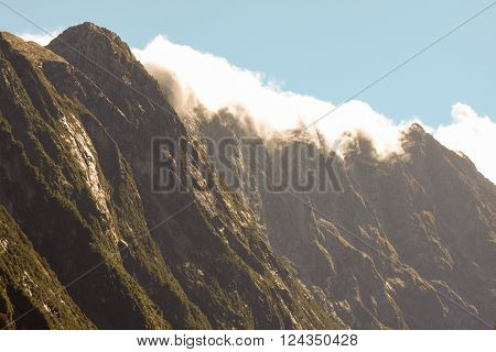 Mountain peaks covered in cloud in Fjordland New Zealand