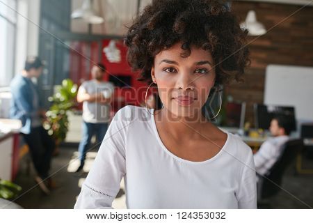 Portrait of a confident young female designer standing in her office with some colleagues in the background. Young african woman standing in office and looking at camera.
