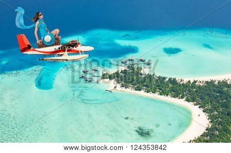 Woman flying above tropical island on seaplane