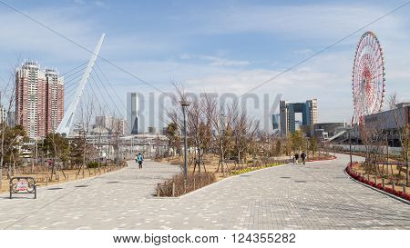 Tokyo - 7 February 2015: The new modern district of Tokyo - Odaiba and beautiful park with paved walkways amusement and people walk in good weather. 7 February Tokyo Japan