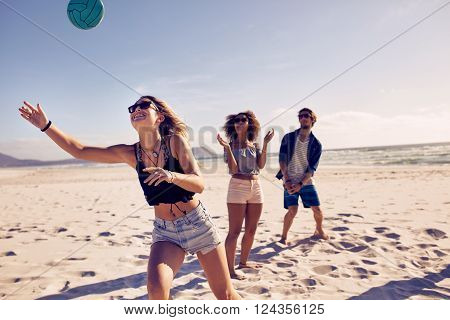 Group of friends playing volleyball on the sandy beach and having fun. Young people on summer holidays playing with ball on the beach.