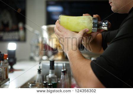 Bartender at work preparing cocktails. Shaking cocktail shaker.
